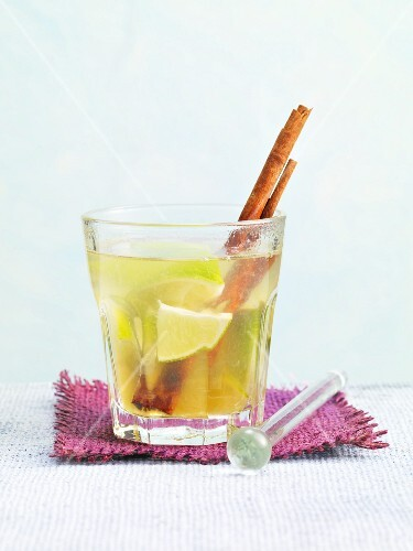 Hot Caipirinha with a cinnamon stick and limes