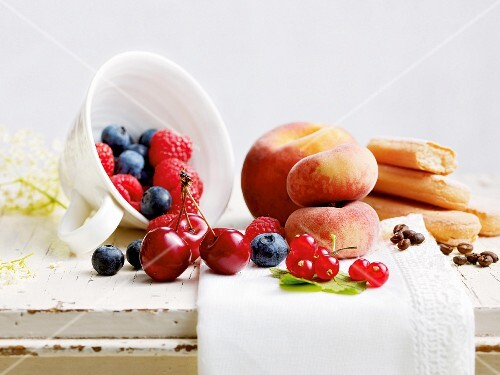 An arrangement of fresh fruit, sponge fingers and coffee beans