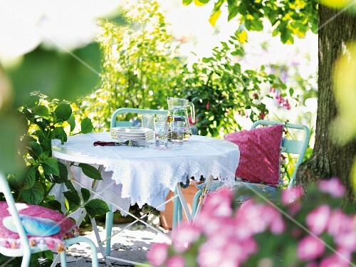 Crockery and glasses on a table in a summery garden