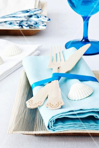 Tourquiose coloured napkins with wooden cutlery and seashells