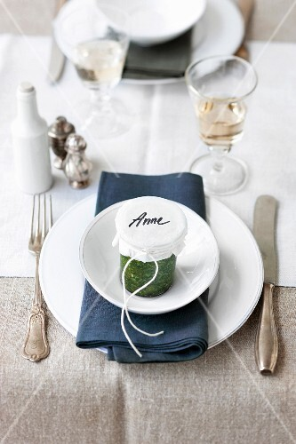 A place setting with a jar of pesto as a guest gift