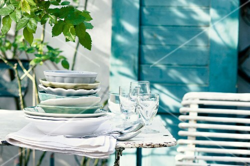 Crockery, glasses and cutlery on a patio table