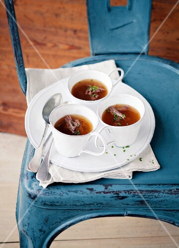 Oxtail broth in cups on a chair