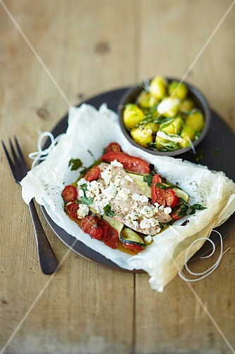 Steamed turkey fillet on a bed of tomatoes and courgette in parchment paper