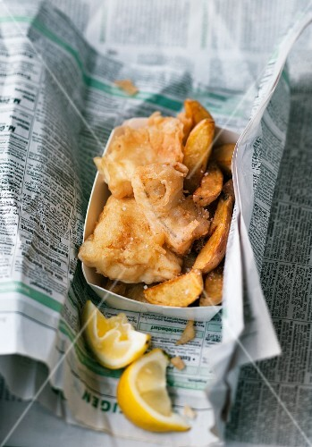 Fish and chips with lemon wrapped in newspaper