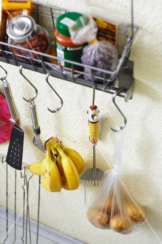 Groceries and utensils hanging from a wall shelf in a student kitchen