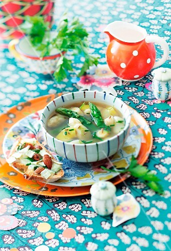 Potato and asparagus soup with herb bread on a colourfully decorated table