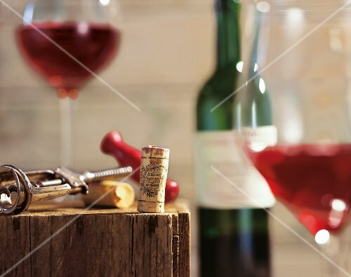 A corkscrew, corks, a bottle of wine and glasses of red wine