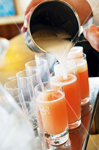 Bellini being poured into glasses
