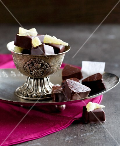 Chilli-pineapple cubes and nougat pralines on a silver plate and in a bowl