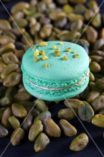 A pistachio macaroon on a pile of pistachio nuts