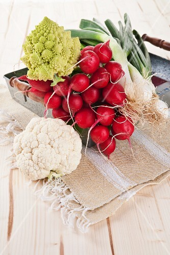 An arrangement of cauliflower, radishes and spring onions