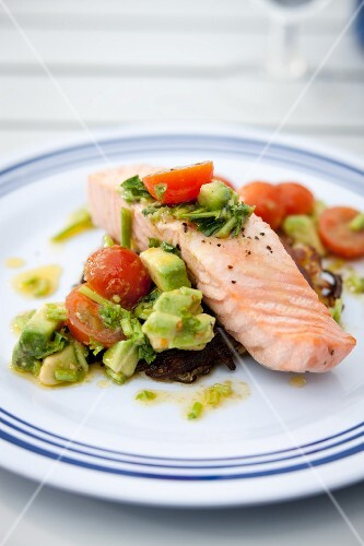 Poached salmon fillet with tomato and avocado salad on a hash brown