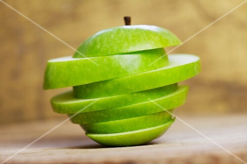 A green apple cut into unequal slices