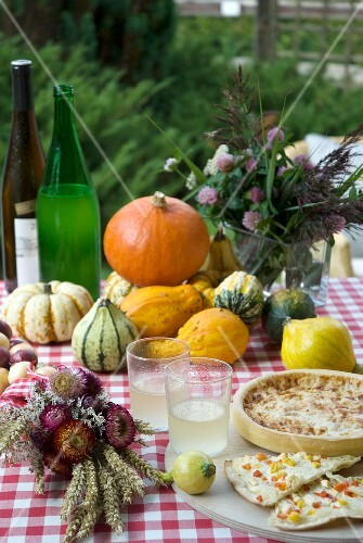 An autumnal tables laid with pumpkins, Federweisser wine and quiche