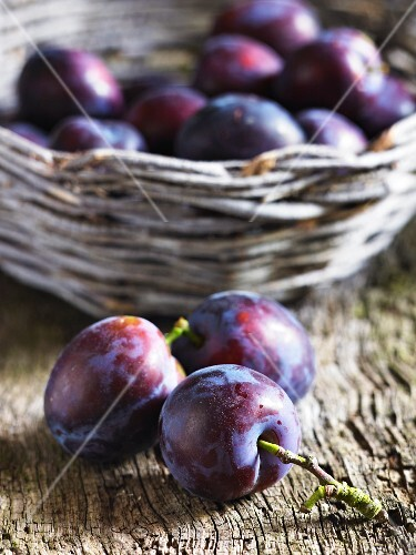 Plums, some in a basket