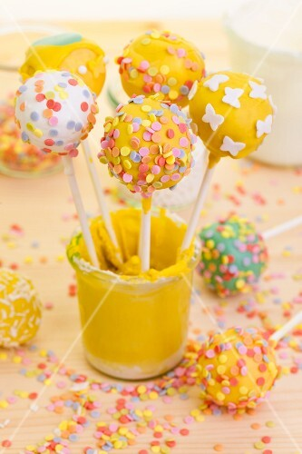 Various cake pops in a glass of yellow icing