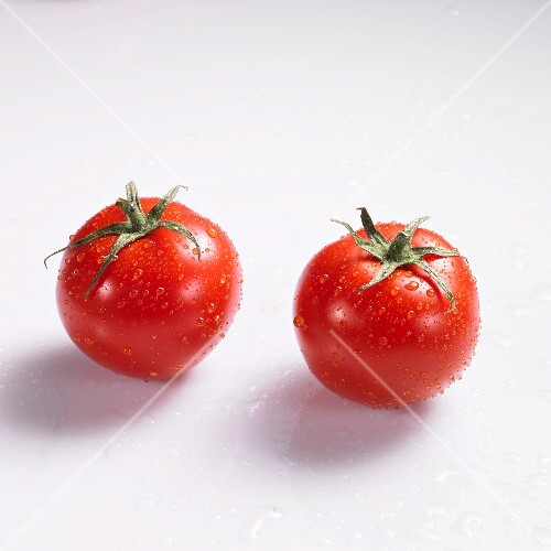 Two tomatoes with drops of water