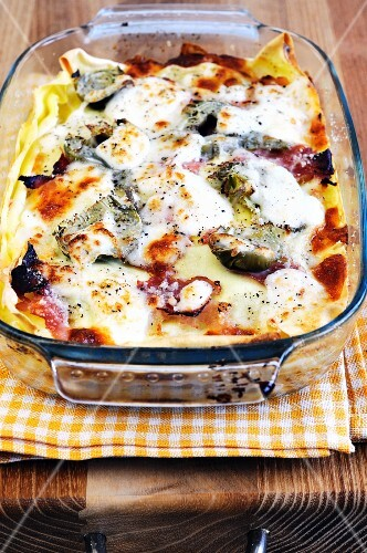 Lasagne with artichokes and ham in a baking dish