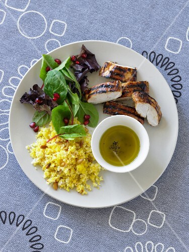 Grilled chicken breast with olive oil, couscous and a mixed leaf salad
