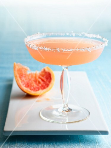 Grapefruit Martini in a Glass with Sugared Rim; Squeezed Grapefruit