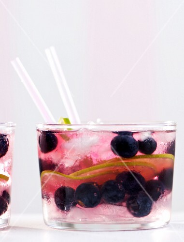 A cocktail made with gin, tonic water, blueberries and lime