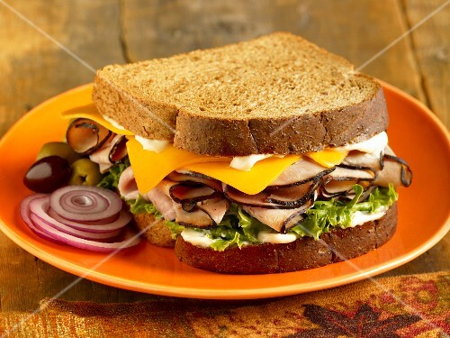 Turkey and Cheese Sandwich on Toasted Wheat Bread; Onion Slices and Olives; On a Plate