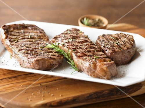 Cuts of Grilled Prime Beef with Rosemary Sprig on a Platter