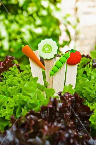 Decorative plant labels with plastic vegetables