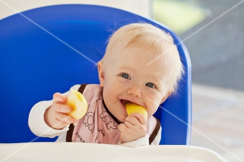 A baby eating an apple