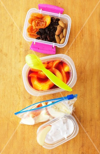 A healthy lunchbox filled with fruit, yogurt and dried fruit