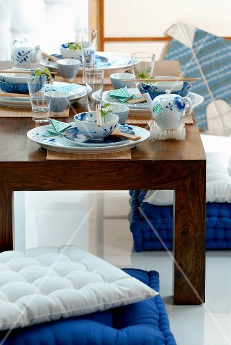 Asian place settings on a low wooden table, and floor cushions in white and blue