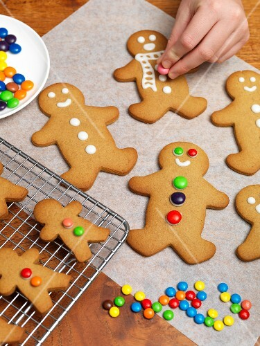 Gingerbread men being decorated with chocolate beans
