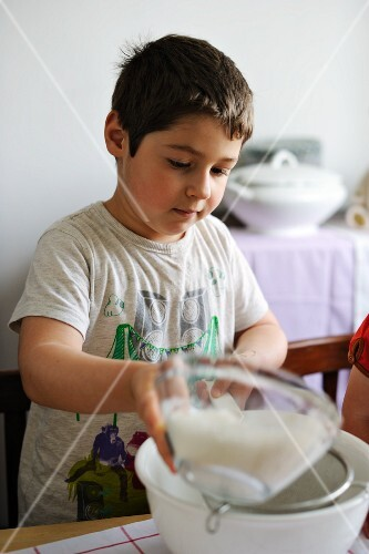 Young boy sifting flour into a bowl
