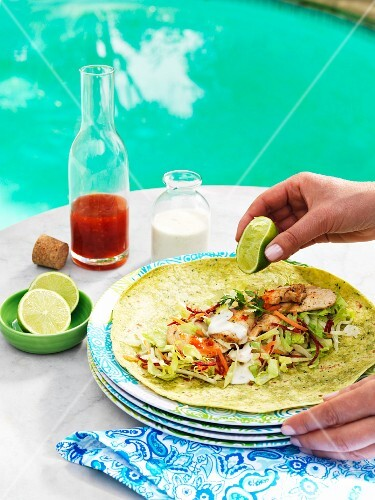 A chicken wrap being drizzled with lime juicce