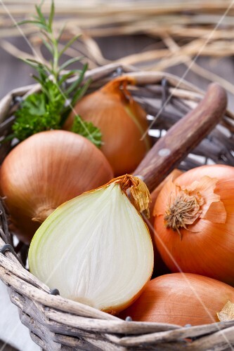 A basket of onions, whole and halved