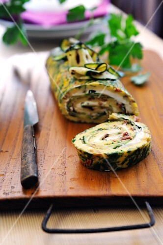 Herb and sun dried tomato omelet roulade filled with ham, cheese and courgette