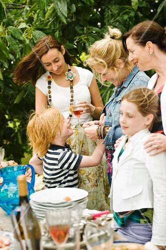 Children and adults standing by the buffet at a garden party