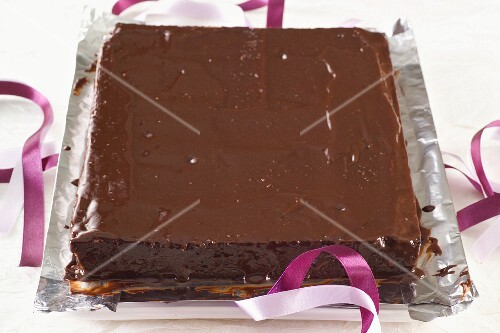 A square chocolate cake on a piece of silver foil