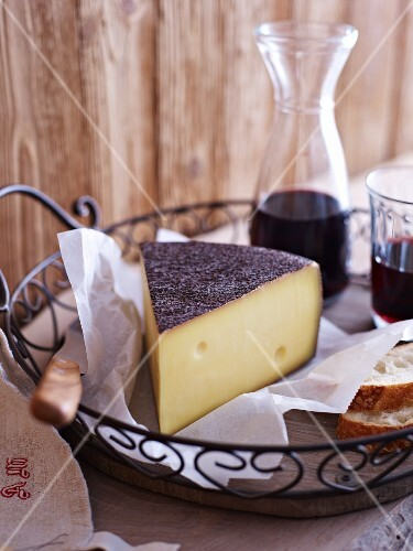 Mountain cheese, baguette and red wine in a wire basket