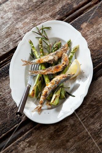 Grilled sardines on a bed of green asparagus with rosemary