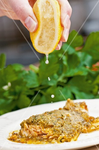 Salmon trout with a herb crust being drizzled with lemon juice