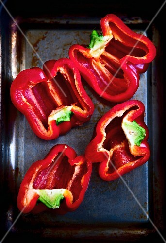 Halved red peppers on a baking tray (seen from above)