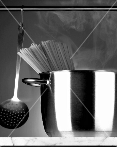 Spaghetti in a stainless steel pot and a hanging ladle