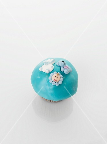 A turqoise cupcake decorated with baby motifs