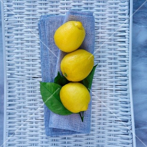 Three lemons on a blue cloth