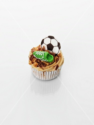 A caramel cupcake decorated with football motifs
