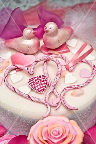 A white cake decorated with hearts, birds, rose petals and a bow