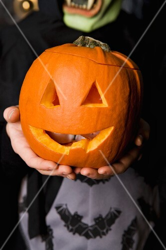 Child holding Halloween pumpkin with a carved face