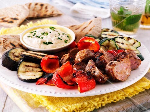 Grill platter with lamb, peppers, aubergines, courgettes, a hummus dip and pita bread